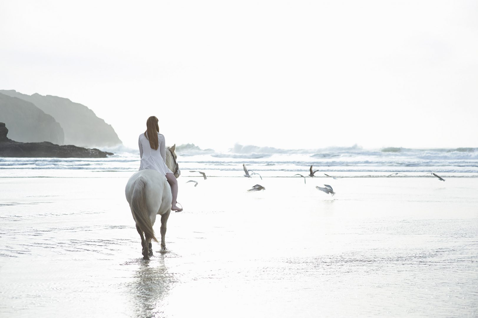 Photograph of a girl riding a horse on a Cornish beach